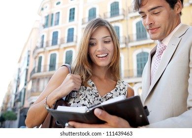 Businessman and businesswoman having a meeting outdoors, in a classic city, and looking at paperwork and smiling.