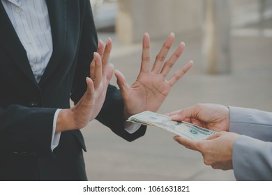 businessman or businesswoman holding stack of money in hand offering bribe, hand gesture rejecting the proposal.
