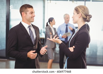 Businessman and businesswoman interacting with each other in office