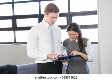Businessman and businesswoman interacting using digital tablet in the office