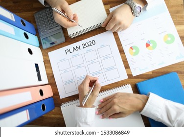 Businessman and businesswoman make work plan 2020 on office table with folder paper background. Business paperwork concept