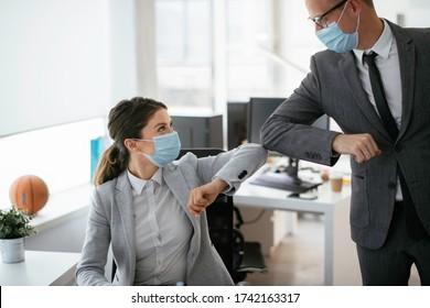 Geschäftsmann und Geschäftsfrau mit medizinischer Maske im Büro. Grüße in Covid-19 Zeit.