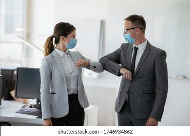 Businessman and businesswoman with medical mask in office. Greetings in Covid-19 time.