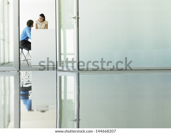 Businessman and businesswoman in meeting viewed through open office door