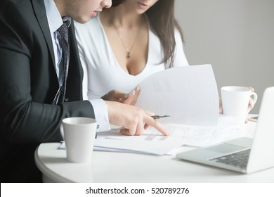 Businessman and businesswoman at office desk, working together with financial documents, preparing proposals, checking the information. Business concept photo.