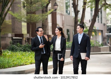 Businessman and businesswoman partner discussing while walking in office building.