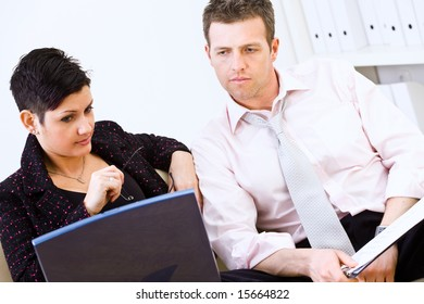 Businessman and businesswoman reviewing documents together on laptop computer at office.