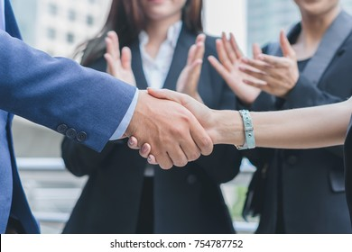 Businessman and businesswoman shaking hand and smiling after discuss new project success, supported by colleagues applauded in cityscape background, business people conceptbusiness concept