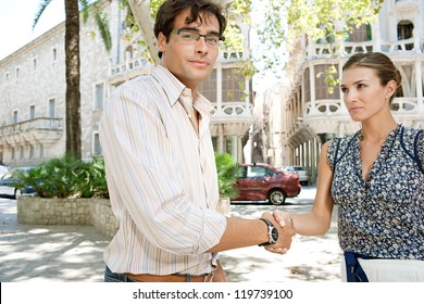 Businessman and businesswoman shaking hands in business agreement while standing near office buildings in a classic city.