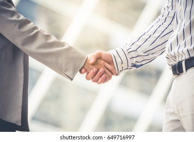 Businessman and businesswoman shaking hands for greeting and meeting at outdoor, teamwork and cooperation concept, vintage tone