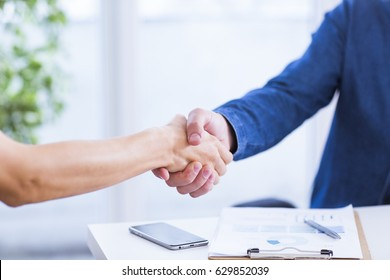 Businessman and businesswoman shaking hands in office.