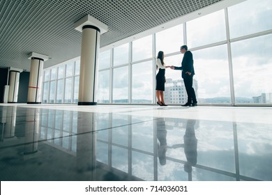 Businessman and Businesswoman shaking hands in office with big panoramic windows concept