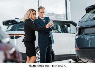 businessman and businesswoman with smartphone choosing new automobile in showroom