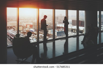 Businessman and businesswoman standing near window of skyscraper, two their male colleagues sitting on armchairs on opposite sides, winter cityscape outside, office interior with reflections