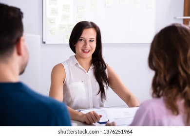 Businessman And Businesswoman Taking Interview Of Young Smiling Woman