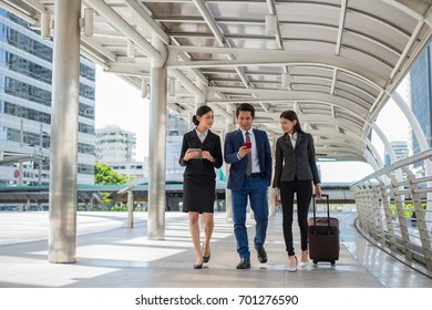 businessman and businesswoman talk and walk together with mobile tablet and luggage on the public street, business trip