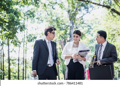 Businessman and businesswoman talking outdoors about their business while holding document report and briefcase and walking through walk way of park after work.