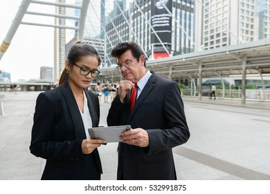 Businessman and businesswoman thinking and using digital tablet in Thailand at Bangkok city