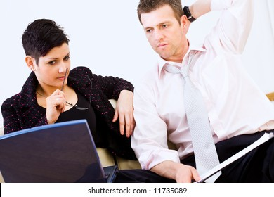 Businessman and businesswoman trying to solve a problem together.