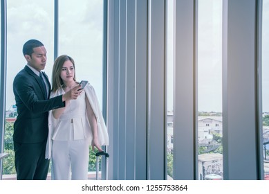 Businessman and Businesswoman use mobile phones to search for flights and check in the airport.Business trip concept
