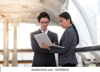 Businessman and businesswoman using digital laptop computer shopping online at Outside Office, partnership business Team Concept. Adhering to respect, teambuilding partnership and alliance concept