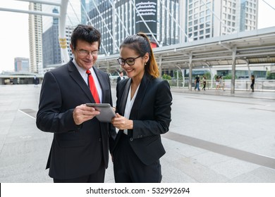 Businessman and businesswoman using digital tablet in front of modern building at Bangkok city