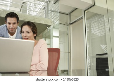 Businessman and businesswoman using laptop at conference table
