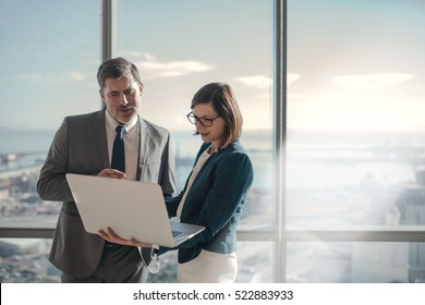 Businessman and businesswoman using a laptop together while standing in front of office building windows overlooking the city