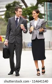Businessman And Businesswoman Walking Along Street Holding Takeaway Coffee
