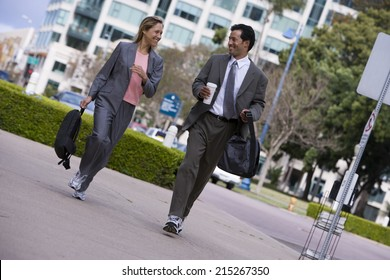 Businessman and businesswoman walking on pavement in city, carrying rucksacks, smiling (tilt)