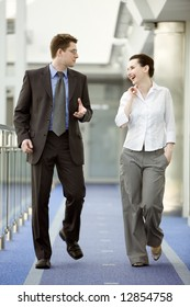 Businessman and businesswoman walking and talking on modern office corridor.