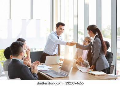 businessman and businesswoman wearing suit and shaking hands (teamwork or partnership concept)