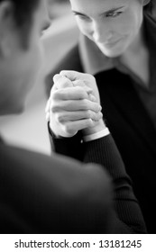 businessman and businesswoman wearing suits sit as they arm wrestle