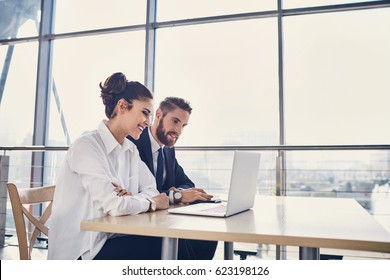 Businessman and businesswoman working with laptop at modern office