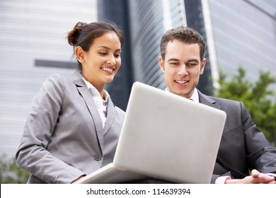 Businessman And Businesswoman Working On Laptop Outside Office