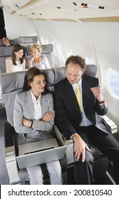 Businessman and businesswoman working on laptop on airplane