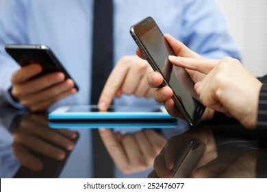 businessman and businesswoman working and using smart mobile phones and tablet computer on meeting