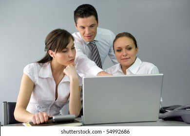 Businessman and businesswomen in front of a laptop computer