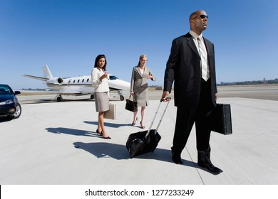 Businessman and businesswomen on runway at airport by executive jet