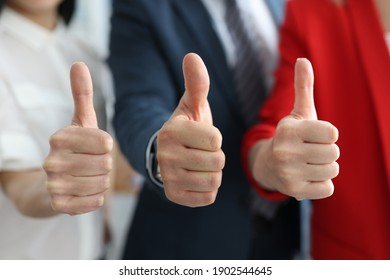 Businessman and businesswomen showing ok gesture with thumbs up. Successful partnership work concept