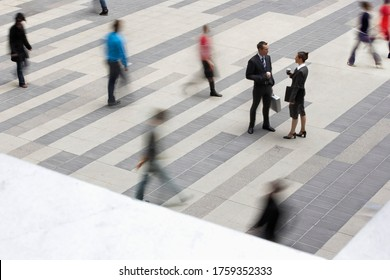 Businessman and businesswomen standing and talking in outdoor plaza people passing elevated view