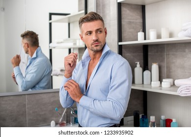 businessman buttoning up blue shirt and looking away in bathroom at home