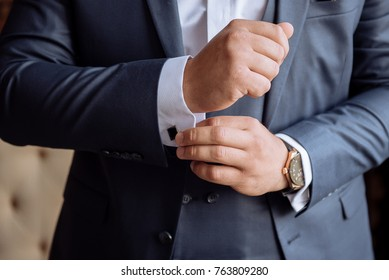The businessman is buttoning his shirt. Cufflinks on a white shirt in a blue jacket ..