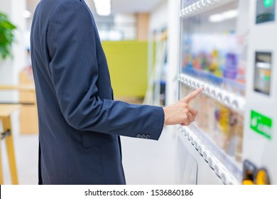Businessman buying juice with vending machine