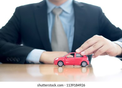 Businessman by a desk holding a toy car.