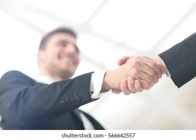 Businessman by handshake invites to cooperation.