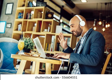 Businessman in a cafe at breakfast making video call with laptop