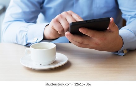 Businessman in a cafe drinking coffee and working on a Tablet PC