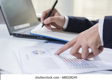 Businessman calculate about cost and charts report on table at home office, calculator on desk of financial planing. Finance concepts.