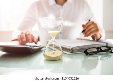 Businessman calculating bill behind sand running through the bulbs of an hourglass